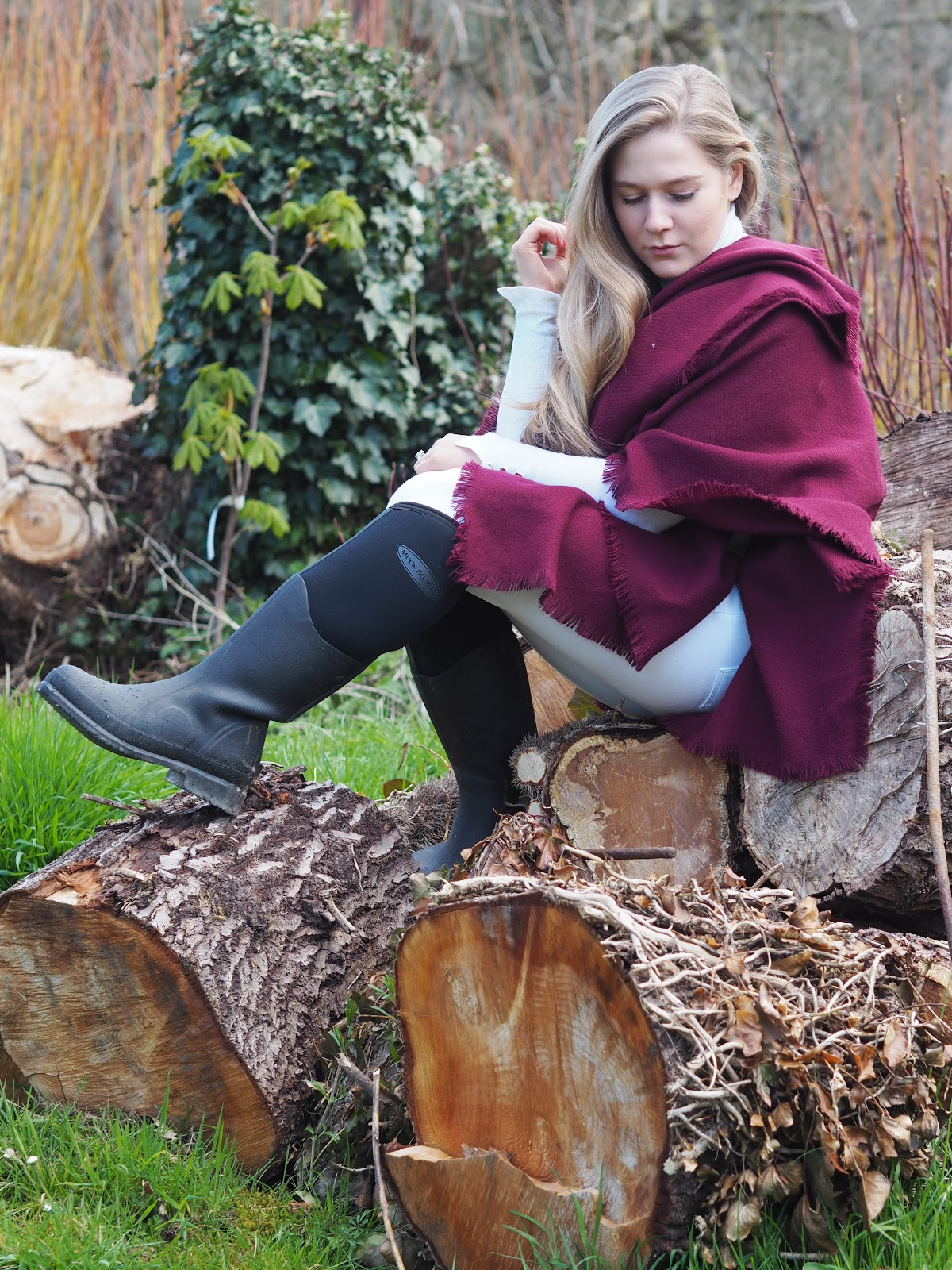 Blonde Girl, Katie Matthews wearing red Reiss cape, White Zara Jeans and Black Muck Boots