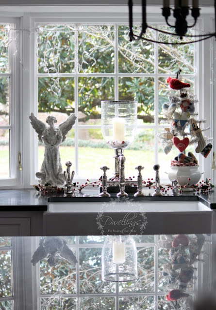 Kitchen window at Christmas with glitter angel, candles and tinsel tree.
