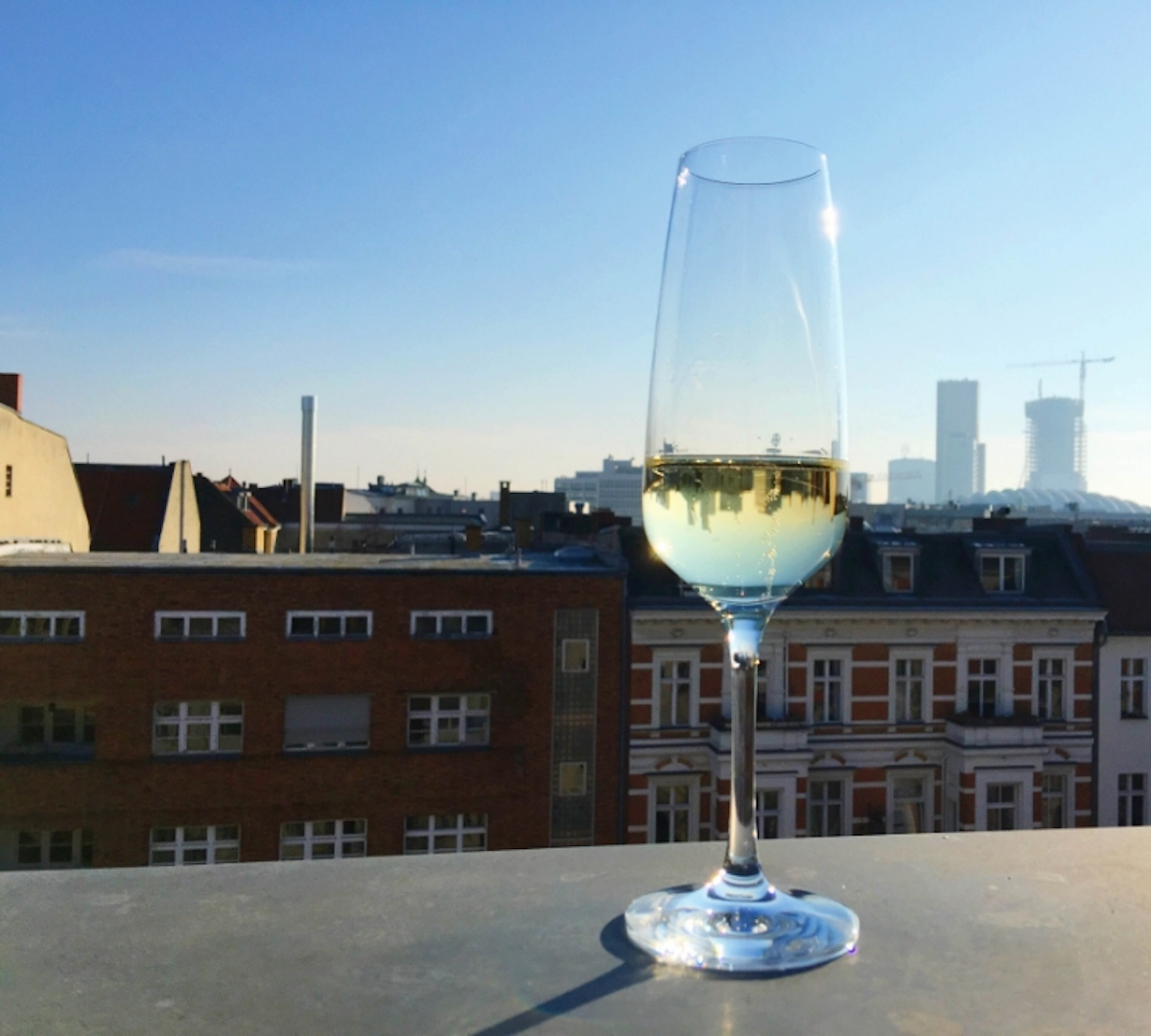 This is a photo of a glass of champagne on the rooftops of Berlin.