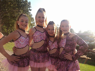 Four young dance girls standing/posing wearing pink and purple dance outfits