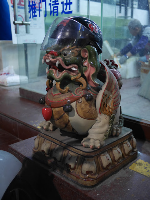 helmet with plastic vizor on top of a Chinese guardian lion