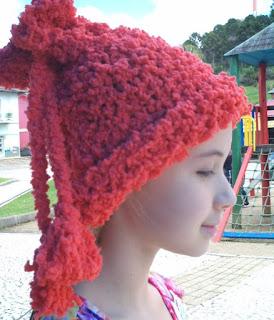 gorro/gola de trico na cor laranja na cabeça de uma menina