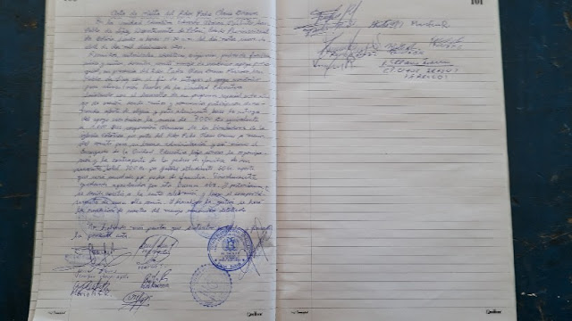 Der Lehrer hat das Geld gezählt und zeigt es den Anwesenden. Dann wird alles in einem Dokument festgehalten, unterschrieben und mit Stempel versehen.