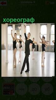 в зале хореограф занимается с учениками, показывает элементы танца