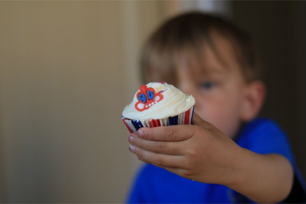 child-holding-out-queens-90th-birthday-cupcake