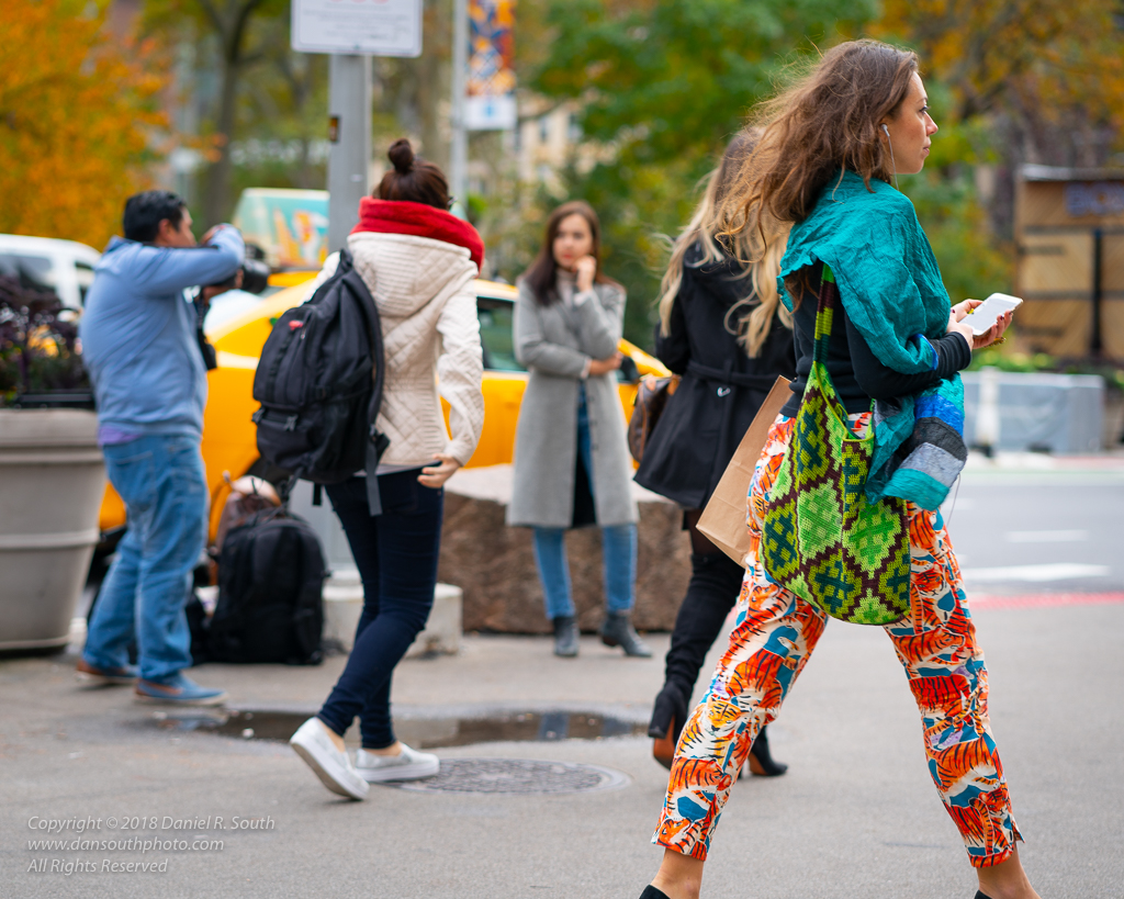 a photo of a pretty woman walking in new york with tiger print pants