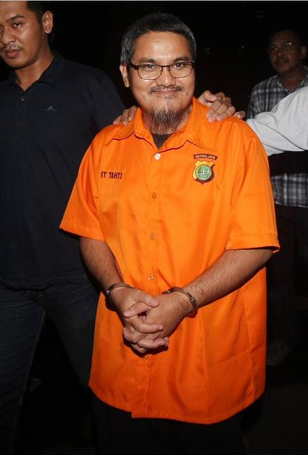 Jonru tampak memakai baju tahanan warna oranye. Tangannya juga diborgol. Meski begitu, Jonru tetap tersenyum