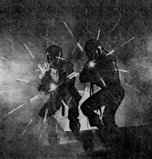 Really bad black and white copy of two dark figures, silhouetted against a bright fog, each with a pistol blazing bright white light and surrounded by a rainbow star