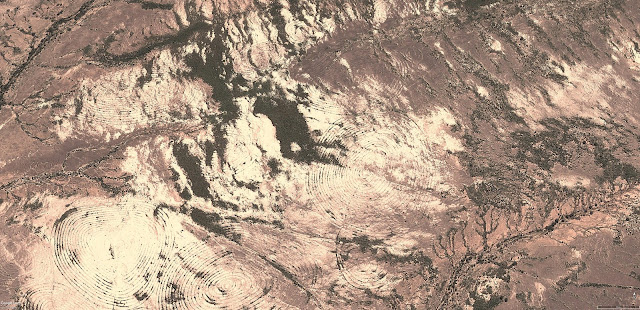 Таинственные геоглифы Намибии, часть 2, Сферы, Спирали и Порталы Вихри Продолжение об удивительных находках в Африке, в пустыне Намибии, сотни гигантских геоглифов в виде спиралей и кольце образных пиктограмм на площади десятков гектар, и никто о них публично не знает, они видны из самолёта и о них продолжают умалчивать. Геоглифы расположены на значительном отдалении от населённых пунктов. Структура геоглифов довольно проста, они сделаны из небольших насыпей до 50 см в высоту и метра в ширину, большинство в виде спиралей, которые сужаются к центру. Главным образом подчёркнута взаимосвязь геоглифов между собой. Когда линия прочерчивающего геоглифа закручивается в центре пиктограммы, то линия не обрывается, линия плавно поворачивает в сторону, выходя за пределы пиктограммы и затем линия закручивается в новый символ. Если учесть особенности климата и ландшафта, так же видно, что спутниковые снимки с 2005 по 2016 год показывают рисунок без изменений. Можно прийти к выводу, что рисунки не сохранились бы более ста лет. В регионе саваны есть постоянная растительность в виде кустарников, которыми обрастают геоглифы, корни растений постепенно разрушали бы рисунки. В регионе ежегодно происходят муссоны, которые влияют на почву. Можно с уверенностью сказать, что геоглифы, не очень древние или возможно появились в 20м веке. Более точно рассказать историю геоглифов, могут лишь полевые исследования. Мало вероятно, создание таких невероятно сложных геоглифов людьми, геоглифы на Плато Наска едва схожи с геоглифами Намибии. Геоглифы расположены рядом с руслом реки, может сложится ложное впечатление, что это некая оросительная система. Но к оросительной системе никакого отношения не имеет. Тем более, что похожие геоглифы и другие сложные сетчатые геоглифические структуры располагаются на разных перепадах высот, например, идут вверх по холму, а затем в низ, ясно, что вода не течет вверх. Конструирование людьми подобного сооружения для неких культовых целей, не выдерживает здравой крит