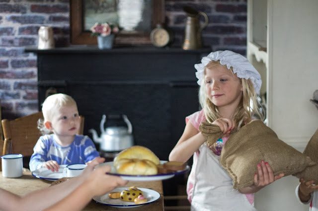 A girl dressed up in a mop cap and apron, a sack of flour, pretend bread and a kettle