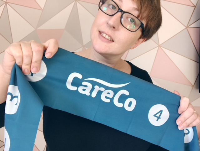 A woman holding up a resistance band with CareCo written on it
