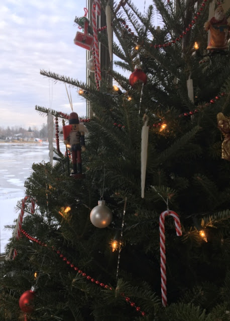 decorated Christmas tree with frozen river in the background