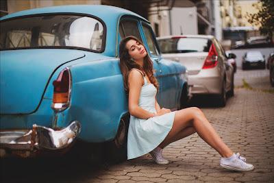 Linda chica apoyada en un coche azul