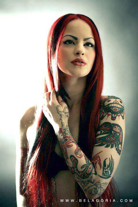Foto de mujer con el cabello rojo largo, lleva tatuajes en los brazos, son tattoos haida tribales