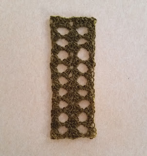 A Tunisian Lace bookmark. it has two columns of spaces in between columns of shell stitches.
