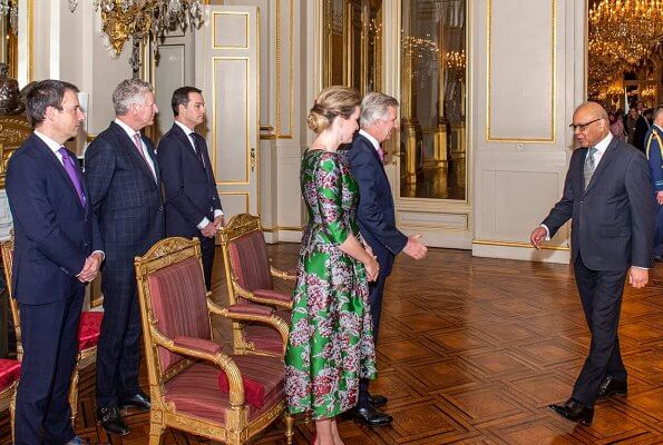 Queen Mathilde wore a green floral-print satin dress by Natan. Édouard, baron Vermeulen is a Belgian fashion designer. Natan red suede pumps