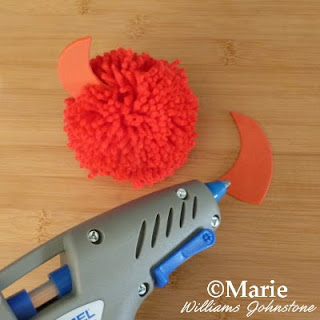 Red pom pom with a glue gun sticking on pieces of craft foam
