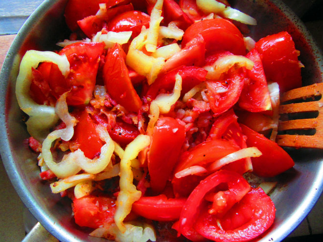 Roasted sea bass with bacon and tomatoes by Laka kuharica: Add the tomatoes, peppers and stir to combine.