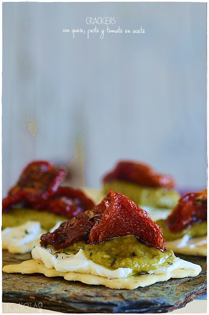 Crackers de queso, pesto y tomate en aceite