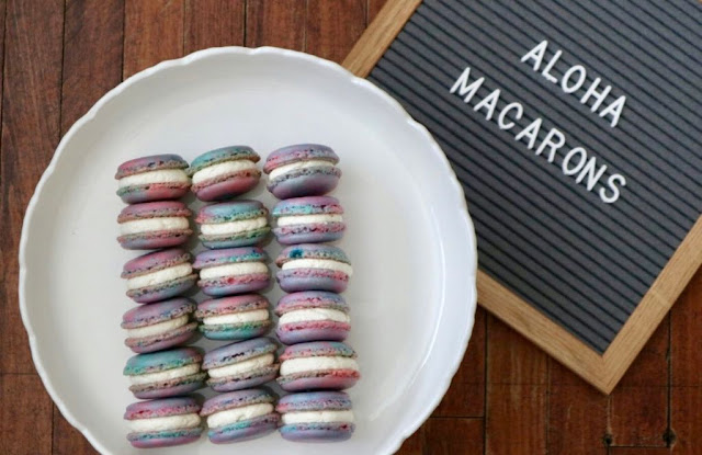 "Letterboard to the right with the words ""Aloha Macarons"" and the Aloha Macarons sitting on a white plate"