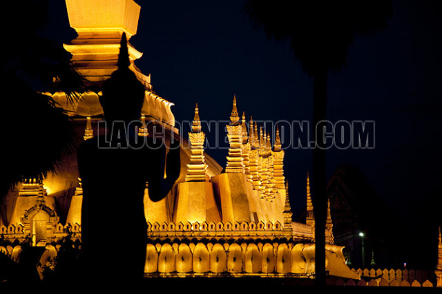 Buddha statue outline overlooks the Tat Luang that's lit up at night