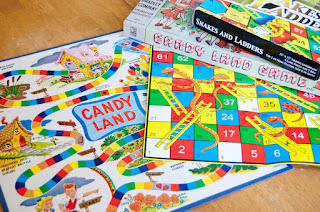 The boards for the games Candy Land and Snakes and Ladders, overlapping on a table, with the boxes for both games stacked on them. These are two of the worst examples of games with no player agency.