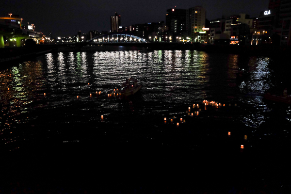 Toro Nagashi Matsuri lanterns floating down the Sumida River towards Komagata Bridge.