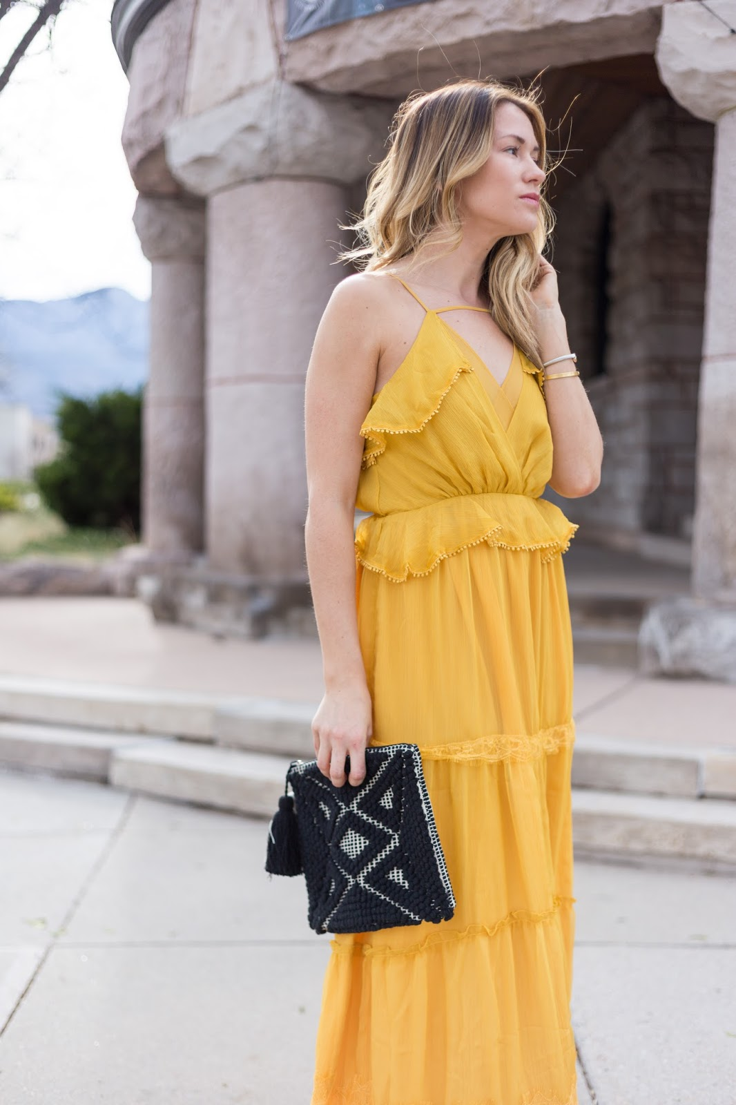 yellow maxi with a black tassel clutch