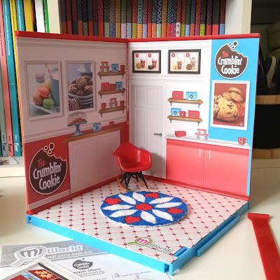 MiWorld cookie shop walls and floor assembled, with a miniature red Eames rocking chair and a round retro rug in colours of red, teal and white on the floor.