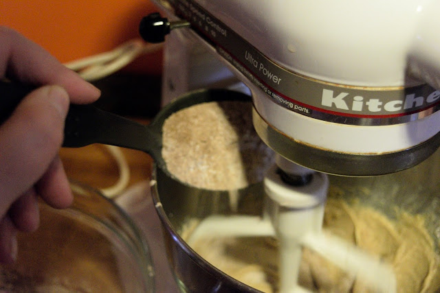 The dry ingredients being added to the creamed butter in the mixer.