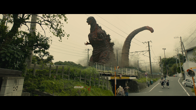 Godzilla towering over people and a bridge