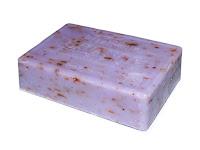 Barra de sabonete artesanal lilás com pequenas sementes. marca em baixo relevo mostra que o mesmo é de lavanda.