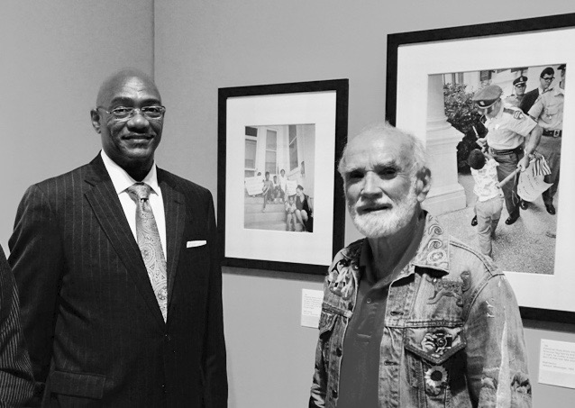 Anthony Quinn,  wearing a suit and a tie, photographed standing by Matt Herron, wearing an embroidered hippie jeans jacket, the the 2014 Museum exhibition commemorating Freedom Summer and featuring photos Herron took of a young Quinn.