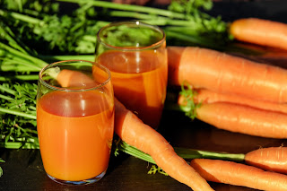 Glass of carrot juice filled next to whole carrots