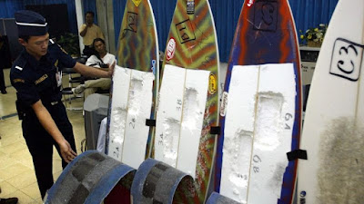 An Indonesian customs officer inspects surfing boards used by Brazil's citizen Rodrigo Gularte to smuggle six kilograms of cocaine. (AAP)