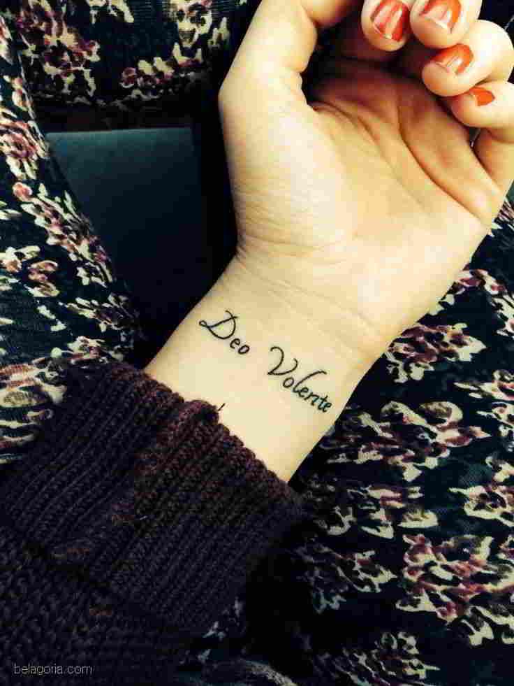 tatuaje de frase en latin deo volente en la muñeca