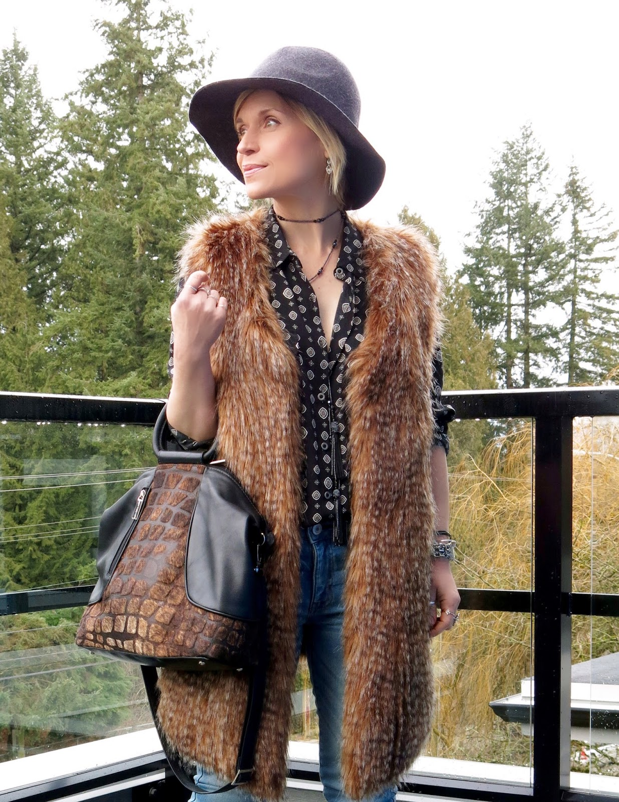 black patterned shirt, long faux-fur vest, Matteo Mio bag, and floppy hat