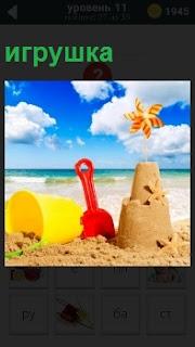 На берегу в песке детские игрушки в виде лопатки и ведра. Сделаны куличи из песка и вставлен флажок