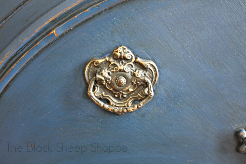 Vintage hardware. Painted in Graphite, distressed and gold highlights added. It looks lovely against the Napoleonic Blue background.