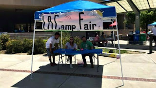 L.A. Camp Fair volunteers and representatives sitting under a blue canopy at the Camp Fair sign-in registration booth at AC Stelle Middle School, Calabasas.