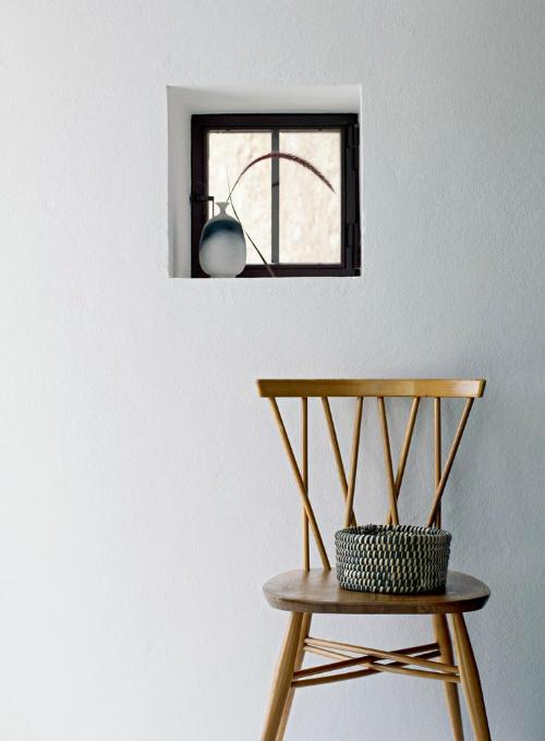 Vor einer weißen Wand steht ein Stuhl dekoriert mit einem Korb