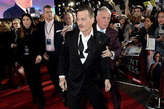 Johnny Depp appears worse-for-wear as security guard seems to prop him up during red carpet arrival