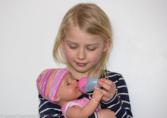 Close up of girl giving BABY born doll water from it's bottle