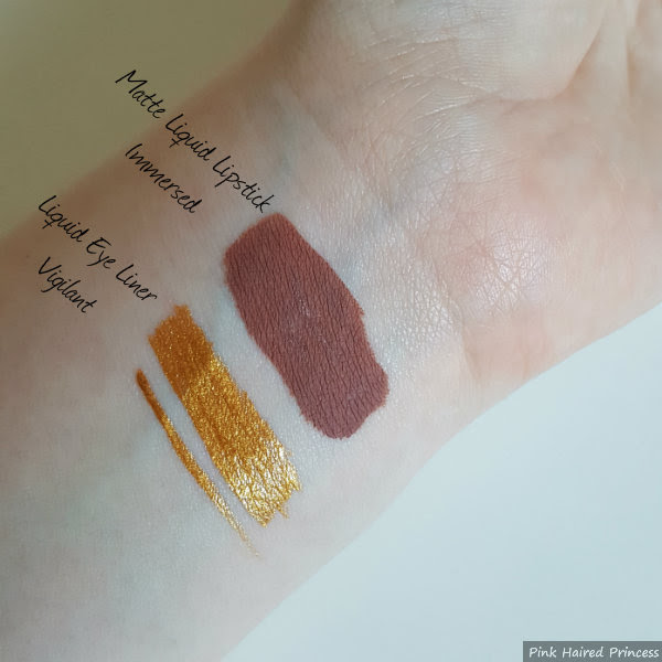 asos matte liquid lipstick in immersed and liquid eye liner vigilant swatches on arm