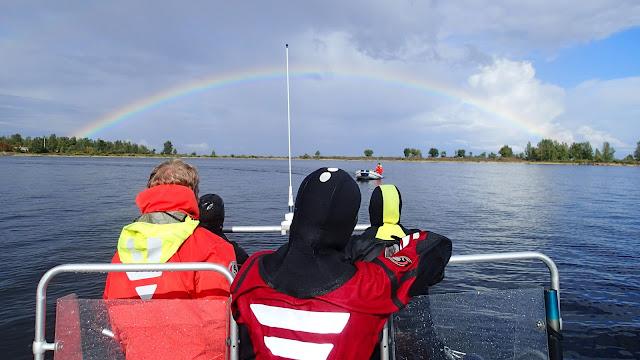 Neljä sukellus- tai pelastautumispukuista henkeä katsoo veneestä sateenkaarta ja kumiveneellä saapuvaa henkilöä