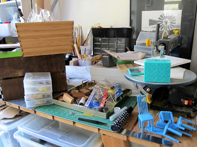 A work bench covered with various one-twelfth scale modern miniatures, accessories and tools.