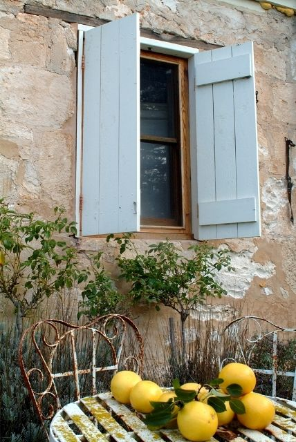 French chateau with blue shutters, iron furniture, and lemons found on Hello Lovely Studio