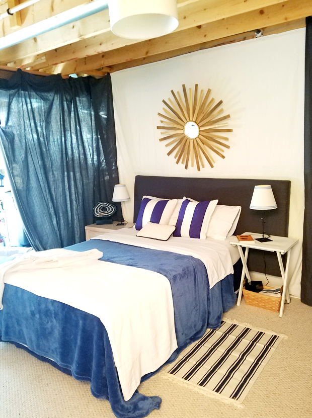 white, blue and wooden tone bedroom with sunburst mirror focal point.