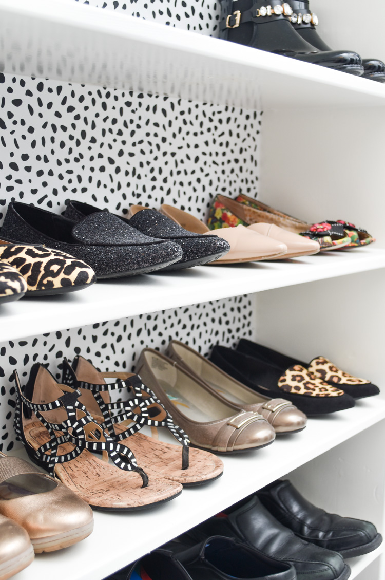 Shoes beautifully organized in a master bedroom closet that only cost $100 to decorate. Love the black and white speckled and spotted wallpaper.