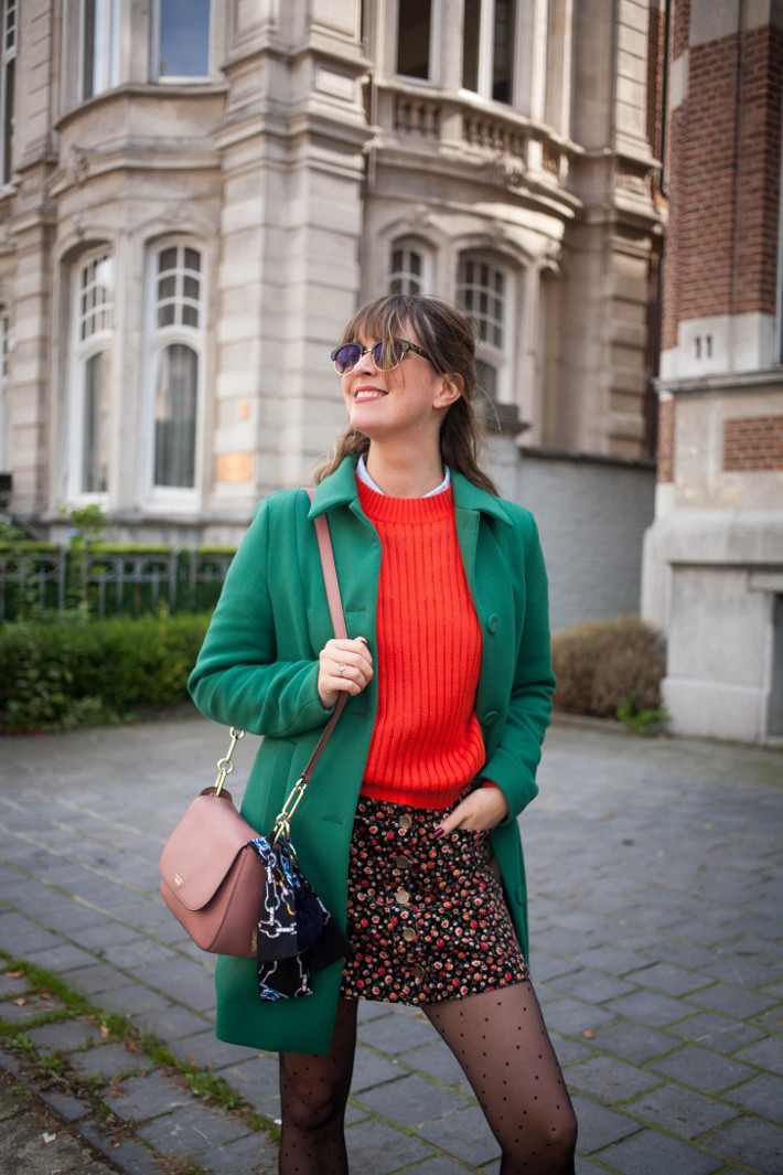 green coat, floral skirt, polkadot tights and pink kate spade bag